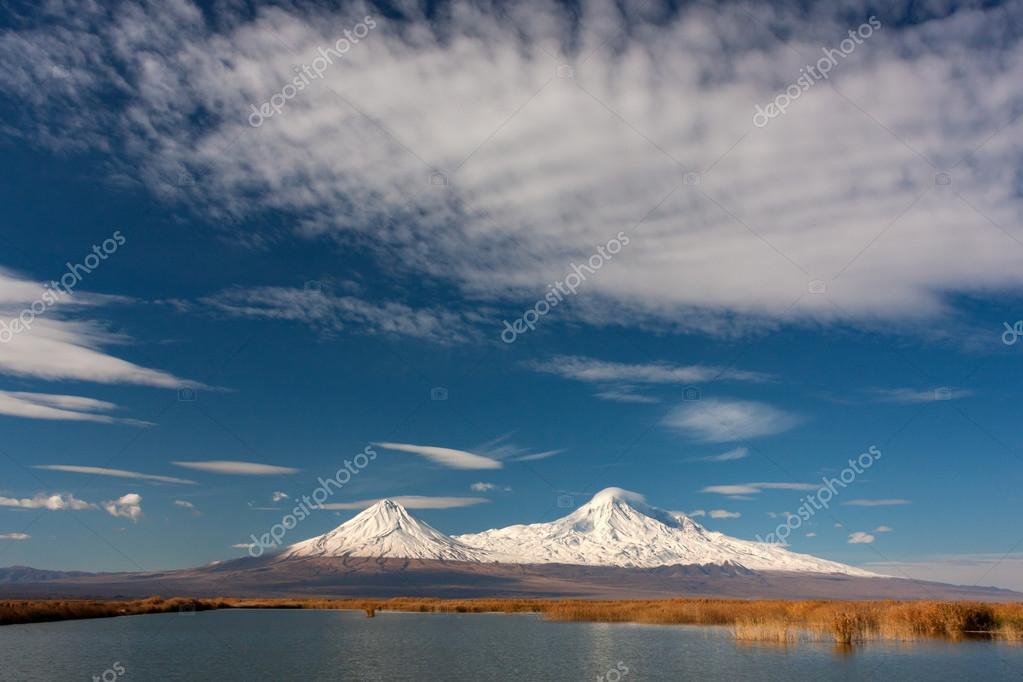 Snowy Ararat mountain in blue sky with foamy clouds