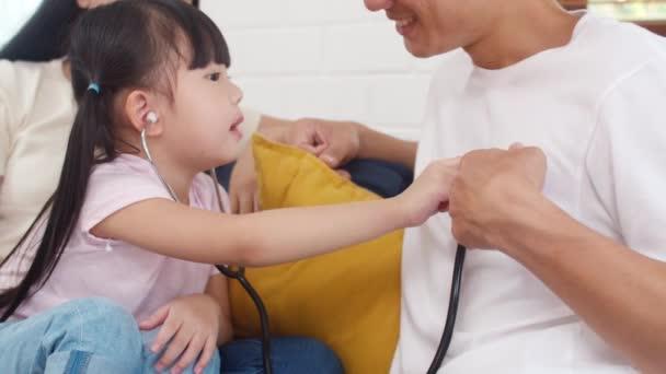 Fröhlich fröhliche asiatische Familie Vater, Mutter und Tochter spielen lustige Spiel als Arzt Spaß auf dem Sofa zu Hause. Selbstisolierung, zu Hause bleiben, soziale Distanzierung, Quarantäne zur Coronavirus-Prävention.