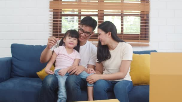 Portrét mladé šťastné asijské rodiny koupil nový dům. Japonská malá školka dcera s rodiči matka a otec drží v ruce klíče sedí na pohovce v obývacím pokoji s úsměvem na kameru.