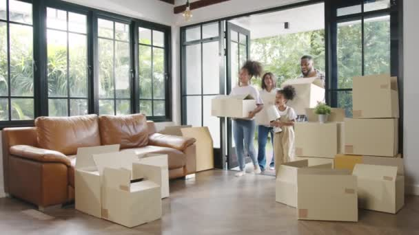 Glückliche afroamerikanische junge Familie kaufte ein neues Haus. Glücklich lächelnd halten Mama, Papa und Kind Pappkartons in der Hand, um das moderne Zuhause zu betreten. Neue Immobilien, Kredite und Hypotheken.
