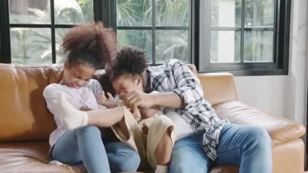 Fröhlich fröhliche afroamerikanische Familie Vater und Tochter haben Spaß Kuschelspiel auf dem Sofa, während Geburtstag im Haus. Selbstisolierung, zu Hause bleiben, soziale Distanzierung, Quarantäne zur Coronavirus-Prävention.
