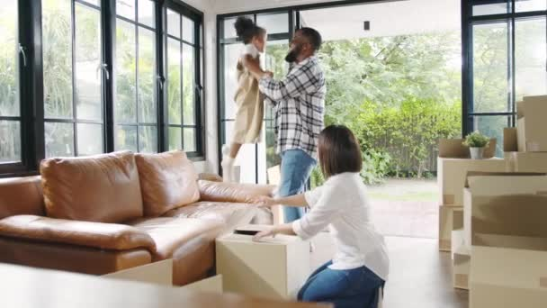 Happy African American young family bought new house. Mom, Dad, and child happy hold cardboard boxes for move object and having fun laugh into modern home. New real estate dwelling, loan and mortgage.
