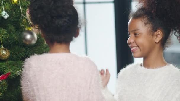 Afroamerikanisches Kind geschmückt mit Schmuck am Weihnachtsbaum zu Weihnachten und Neujahr zu Hause. Weihnachtsfeier Veranstaltungsvorbereitung oder Winterferien Festival Indoor-Party. Nahaufnahme.