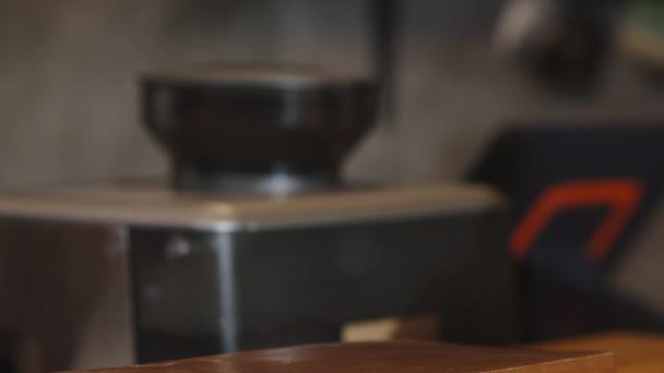 Junge asiatische Barista, die hinter der Theke im Café-Restaurant steht, serviert heißen Kaffee-Pappbecher zum Mitnehmen. Eigentümer Kleinunternehmen, Essen und Trinken, Service-Konzept.