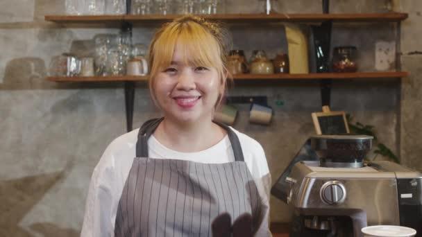 Porträt junge asiatische Barista glücklich lächelnd im städtischen Café. Kleinunternehmer Koreanisches Mädchen in Schürze entspannen sich und lächeln in die Kamera, die im Café am Tresen steht.
