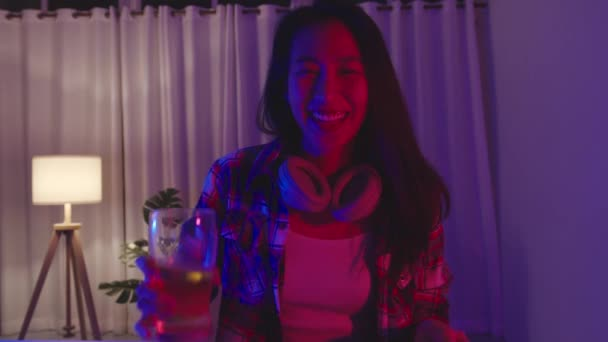 Young Asia lady drinking beer having fun happy moment disco neon night party event online celebration via video call in living room at home. Social distancing, quarantine for coronavirus prevention.