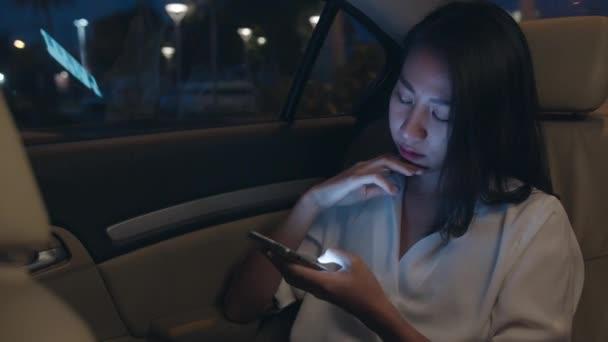 Erfolgreiche junge asiatische Geschäftsfrau in modischer Bürokleidung arbeitet spät mit dem Smartphone auf dem Rücksitz des Autos in der urbanen modernen Stadt in der Nacht. Menschen mit Burnout-Syndrom.