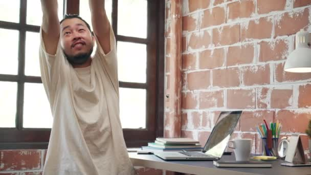 Freelance Asia guy stretching his body because feel tired after working on laptop in living room at house. Working from home, remotely work, social distancing, quarantine for coronavirus prevention.