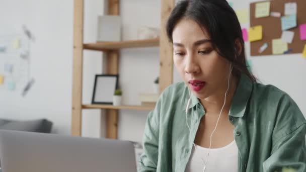 Asiens Geschäftsfrau spricht per Laptop mit Kollegen in Videotelefonaten über ihre Pläne, während sie von zu Hause aus im Wohnzimmer intelligent arbeitet. Selbstisolierung, soziale Distanzierung, Quarantäne zur Coronavirus-Prävention.