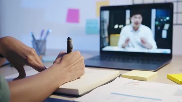 Asiatische Geschäftsfrau unterhält sich per Laptop mit Kollegen in einem Videotelefonat im Wohnzimmer über den Plan. Nachtarbeit, Fernarbeit, soziale Distanzierung, Quarantäne für Coronavirus.