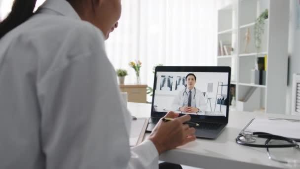 Mladá Asiatka doktor v bílé lékařské uniformě pomocí notebooku mluvení videokonferenční hovor se starším lékařem na stole ve zdravotní klinice nebo v nemocnici. Sociální distancování, karanténa pro virus korony.