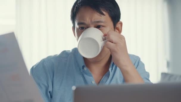 Szabadúszó ázsiai srác alkalmi viselni laptopot és kávét inni a nappaliban a házban. Otthonról való munkavégzés, távoli munkavégzés, távoktatás, társadalmi távollét, karantén a koronavírus megelőzése érdekében.
