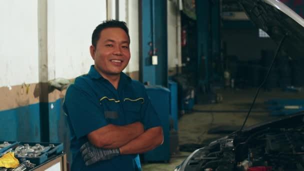 Profesionální automechanik se dívá na kameru a usmívá se na opravárenskou stanici. Dovedný Asiat v uniformě opravuje auto v mechanické garáži v noci. Údržba automobilů.
