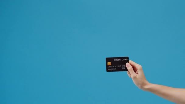 Mladá žena ruka ukazuje kreditní kartu pro nakupování on-line přes modré pozadí ve studiu. Kopírovat prostor pro umístění textu, zpráva pro inzerci. Reklamní prostor, makléřský propagační obsah.