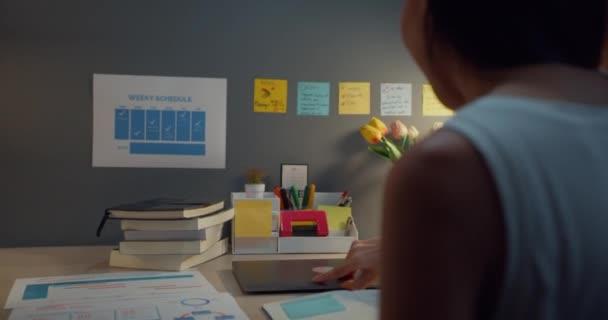 Die junge asiatische Geschäftsfrau, die freiberuflich Laptop-Computer öffnet, macht sich bereit, nachts auf dem Holztisch im Wohnzimmer mit der Arbeit zu beginnen. Arbeit von zu Hause aus, aus der Ferne, soziale Distanz Quarantäne für Coronavirus.