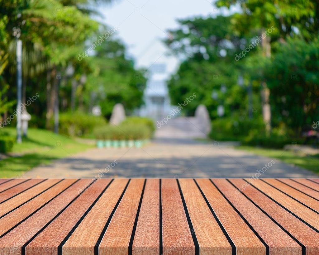 Wooden board empty table in front of blurred background. Perspective brown wood with blurred people activities in park - can be used for display or montage your products. spring season.