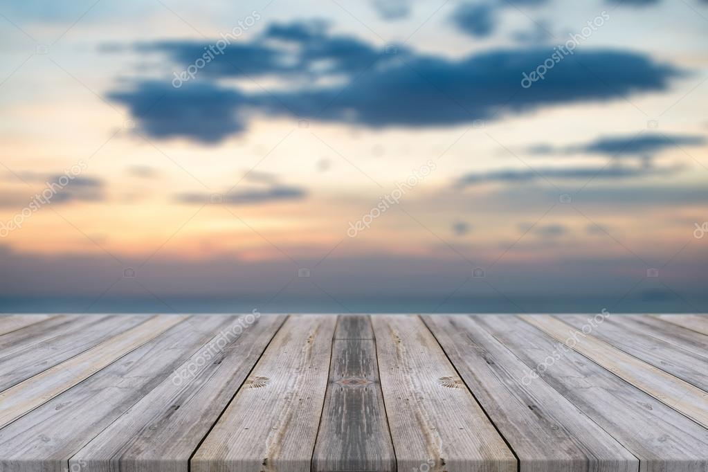 Wooden board empty table in front of sunset background. Perspective wood floor over sea and sky - can be used for display or montage your products. beach & summer concepts.