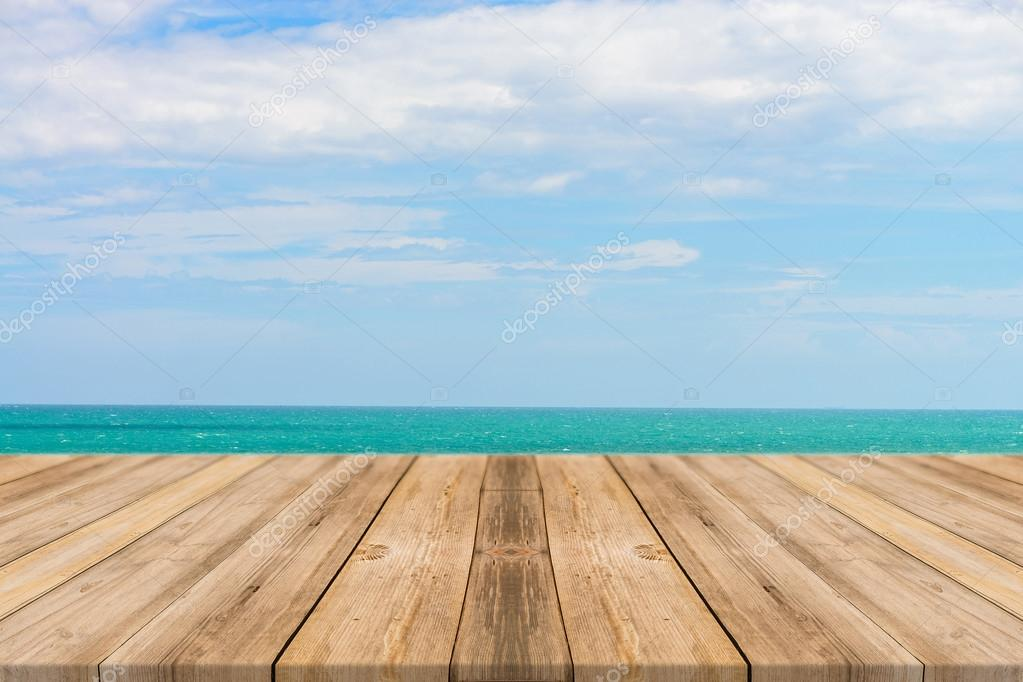 Vintage wooden board empty table in front of blue sea & sky background. Perspective wood floor over sea and sky - can be used for display or montage your products.
