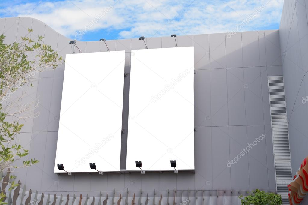 blank poster board wall in modern shopping mall on a cloudy day with