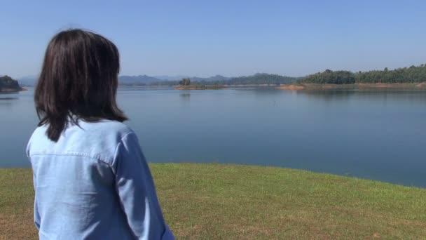 Mladá žena stojí na okraji jezera a vypadá na kameru a úsměvy.