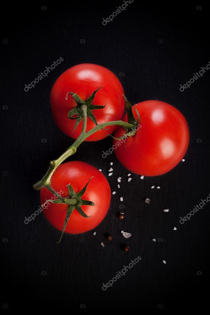Fresh tomatoes on black stone background