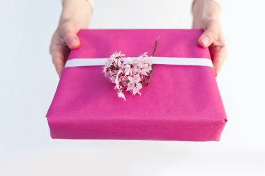 Woman holding gift with pink paper