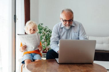 Grandpa and grandson by laptop