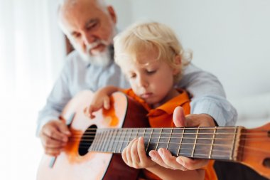 Grandfather and grandson playing guitar