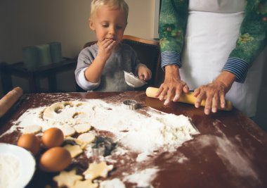Little boy with grandmother preparing and eating Christmas cookies