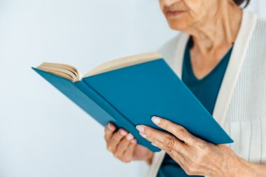 Closeup of old woman reading book