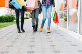 Fotografia Tre ragazze che camminano con i sacchetti di shopping