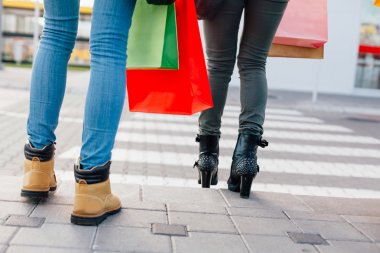 Closeup of two girls with shopping bags crossing the street