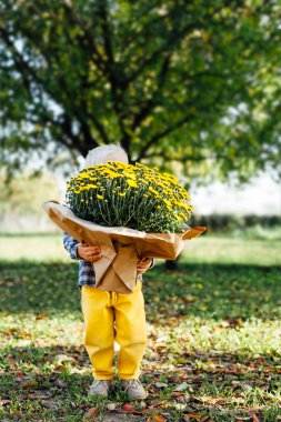 Child with a yellow pants holding a large bouquet of yellow flow