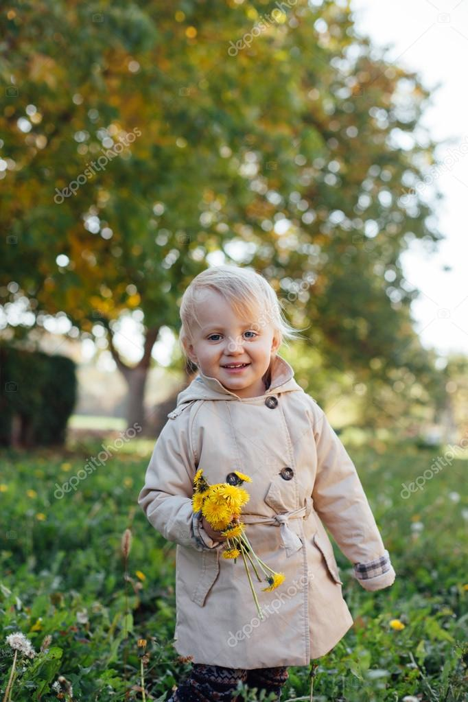 Cute little girl holding yellow flowers