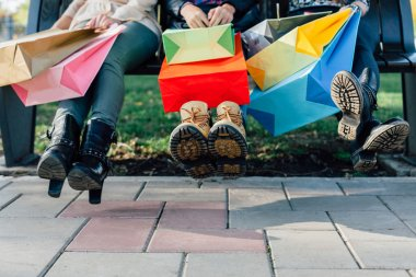 Three girls with colorful shopping bags having fun with shoes