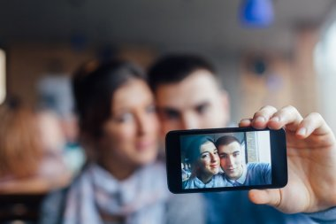 Young couple taking photos of themselves