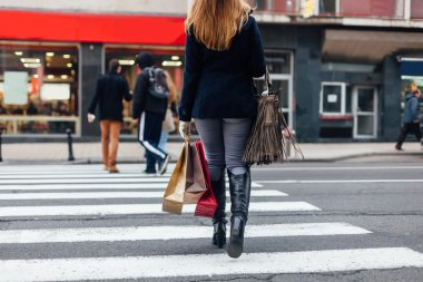 Woman crossing the street at the pedestrian crossing