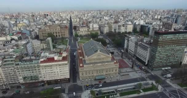 Aerial Drone scene of Colon theatre in Buenos Aires, Argentina, in the morning. 9 de Julio main Avenue, 9 of july. Traffic and people going to work. Camera aerial panning.