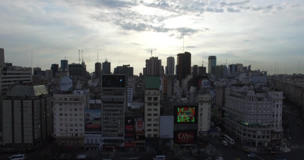 Drohnen-Szene eines Obelisken in buenos aires, Argentinien, bei Sonnenaufgang am Morgen. 9 de julio Hauptstraße, 9. Juli. Verkehr und Menschen, die zur Arbeit gehen. Kamera fährt nach links und lässt den Obelisken erscheinen.