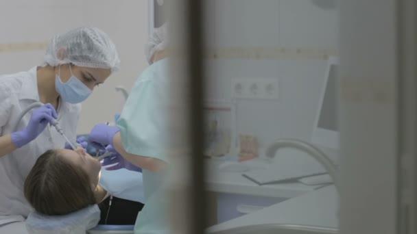 Zubaři a zubní asistent pracuje na pacienty zuby v reálné zubní chirurgii