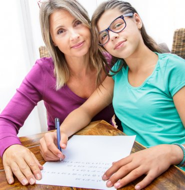 pretty teen girl doing its homework in complicity with her mother