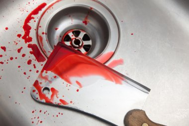bloody cleaver in a sink