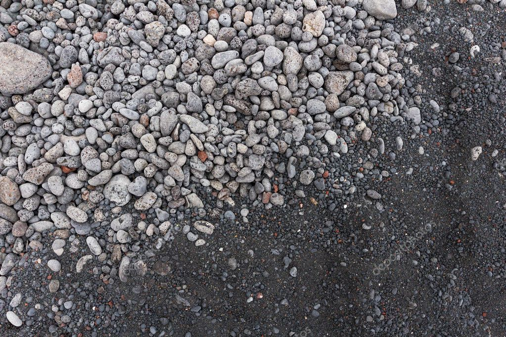 contrast between gray stones and volcanic black sand on the beac