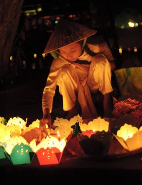 Two small kids selling handmade lanterns to tourists in the streets at July 23, 2013 in Hoi An, Quang Nam, Vietnam.