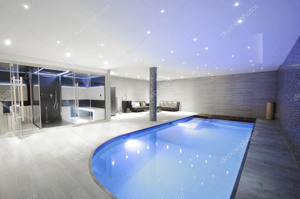 Overdekt zwembad met verlichting en een hoek voor rest ontspannend ...