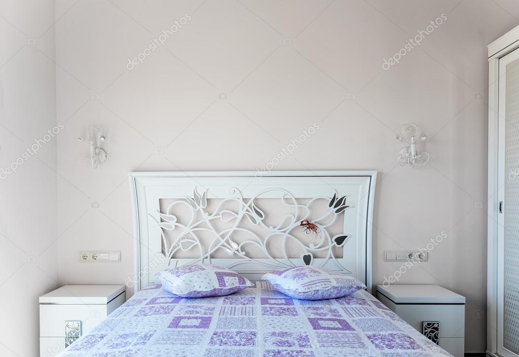 Un letto in una camera da letto. cuscini testiera e viola. due