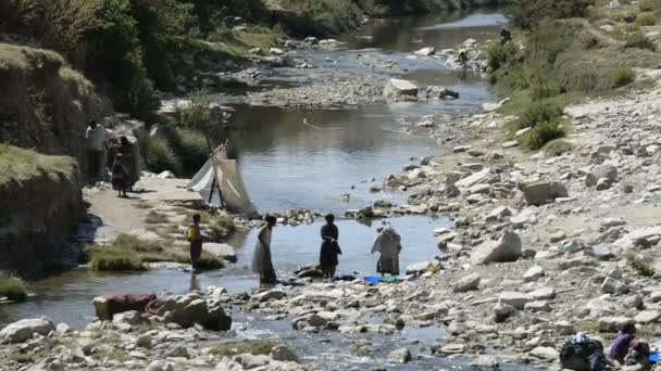Women clean the clothes in rural lake
