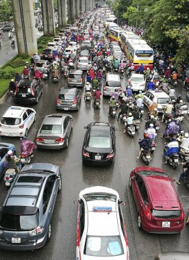 Many cars and motorbikes are stuck in a traffic jam