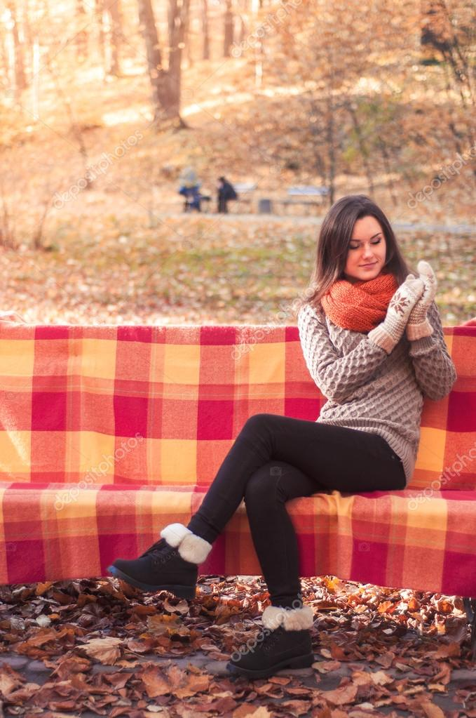 Young beautiful woman in a knitted sweater sitting on a bench in an autumn park
