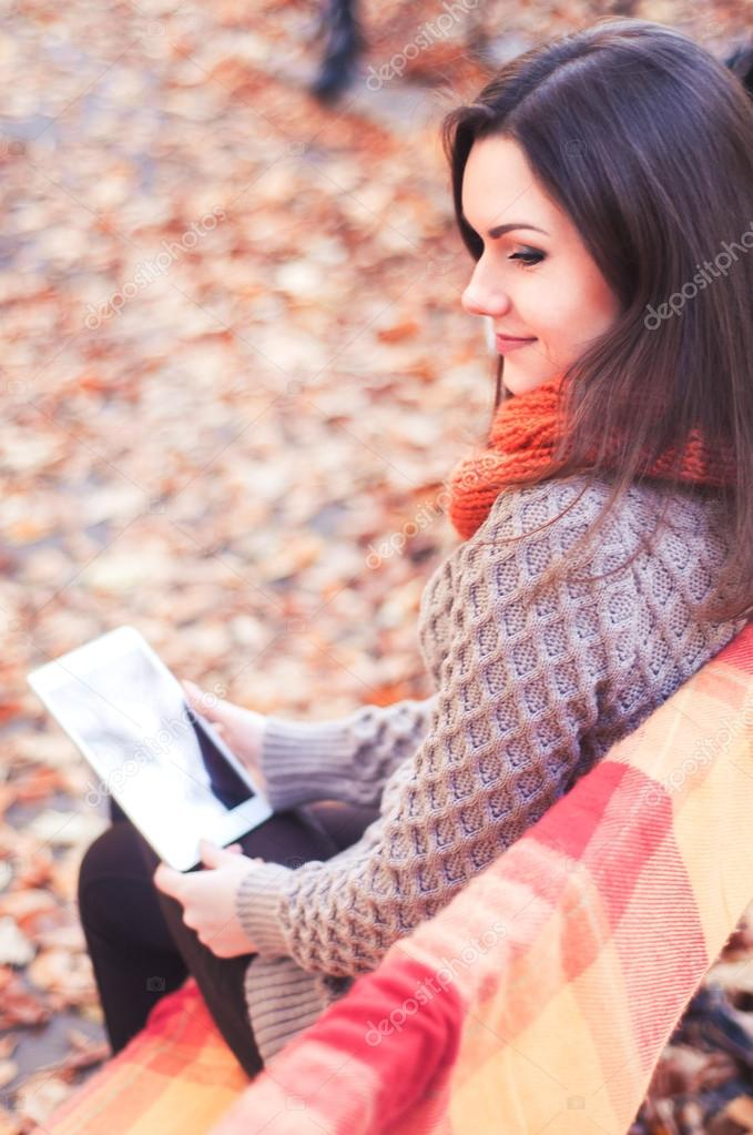 Attractive woman sitting on a bench with a tablet